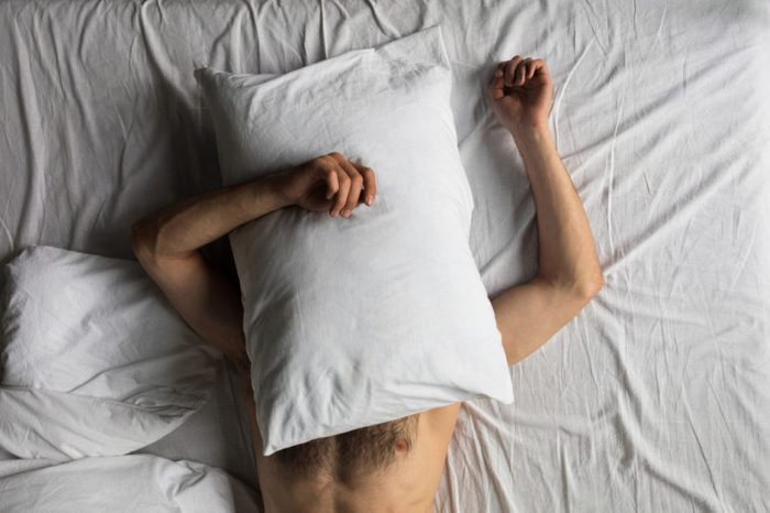 top view of shirtless man hiding face with pillow while sleeping in bed