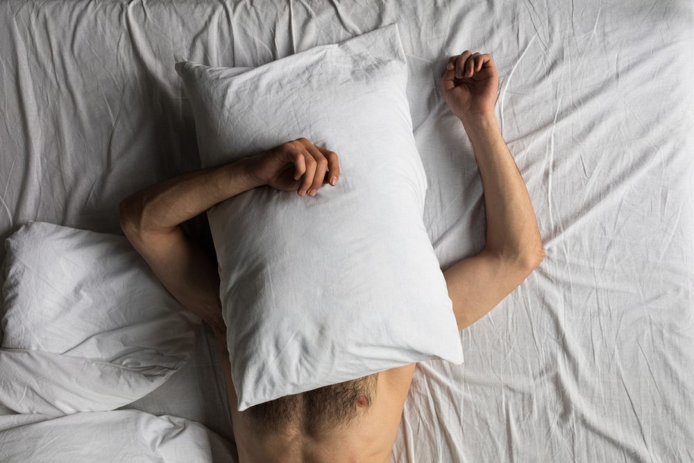 man with pillow over his head