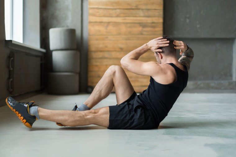 Young man workout in fitness club. Closeup portrait of caucasian guy making exercise, sit-ups and cross crunches for abs muscles, training indoors