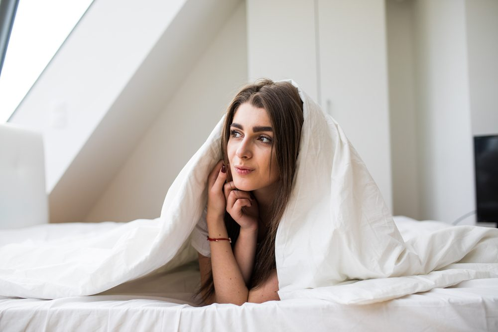 Smiling woman under a duvet in her bedroom