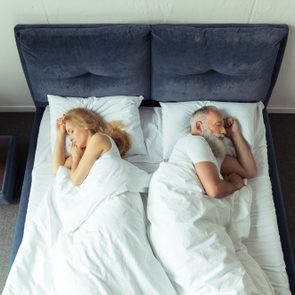 top view of couple sleeping back to back in bed