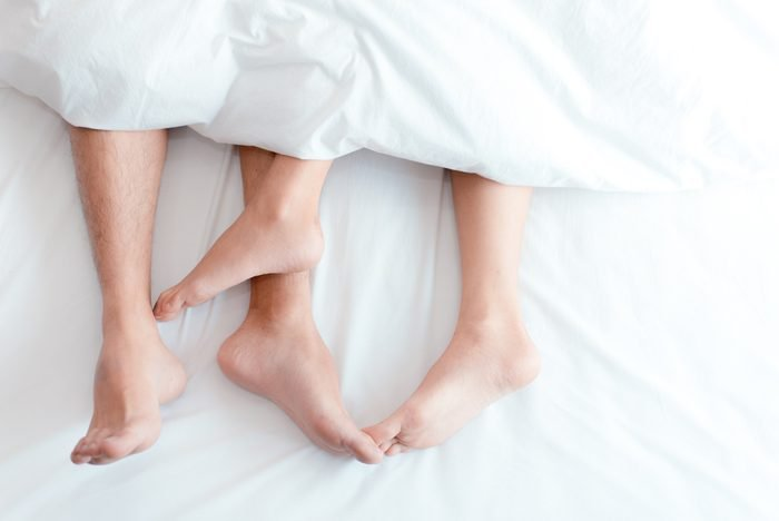 Close up on feet of couple on the bed. Man and woman make love under the blanket or bed sheet. Sex on vacation theme. Valentine and Honeymoon of lovers concept. Top view