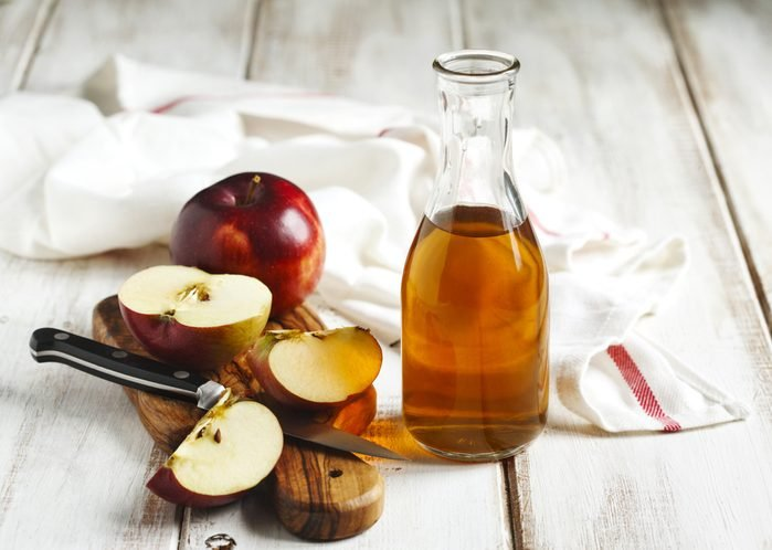 Apple vinegar in a carafe next to cut apples
