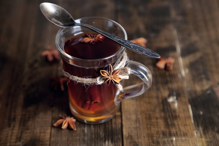 Hot beverage in glass cup with fruits and spices, on wooden background