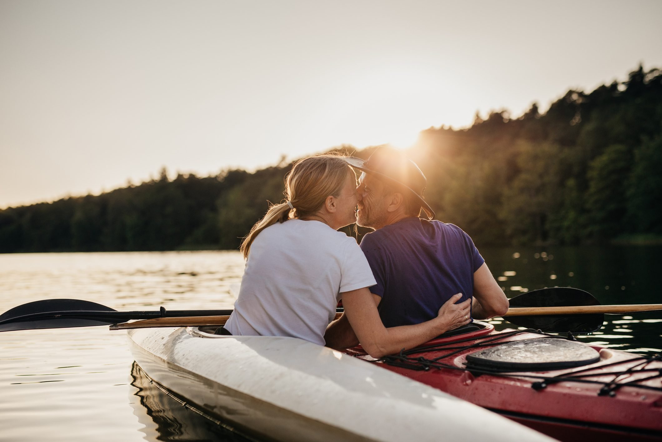 couple kissing while kayaking during sunset