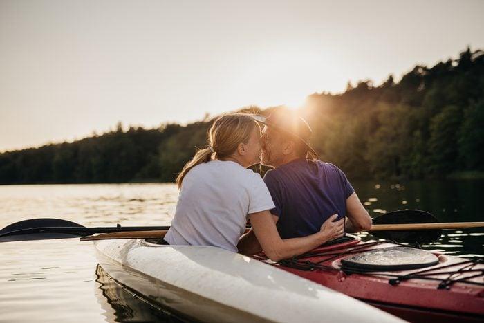 couple kissing while kayaking during sunset