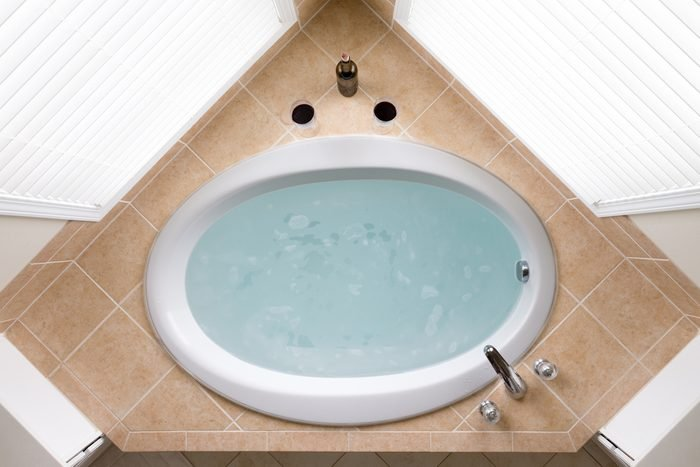 Stylish corner oval bathtub filled with fresh clean water in a brown tile surround flanked by two windows, overhead view
