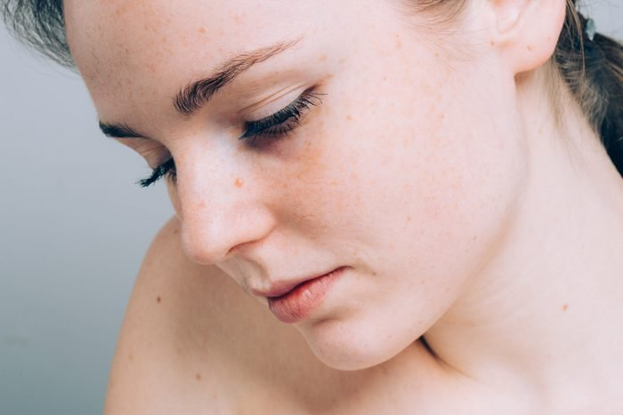 Young beautiful freckles woman face portrait with healthy skin