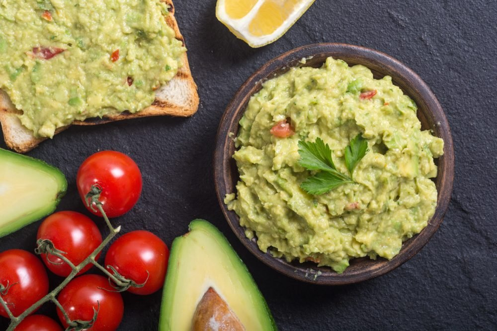 Guacamole with ingredients : avocado , lemon and tomatoes
