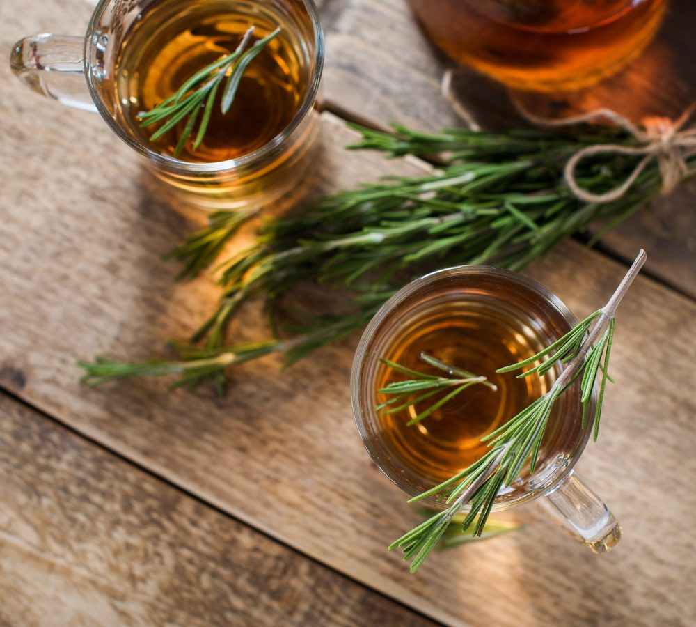 Herbal kombucha tea with aromatic rosemary on wood table