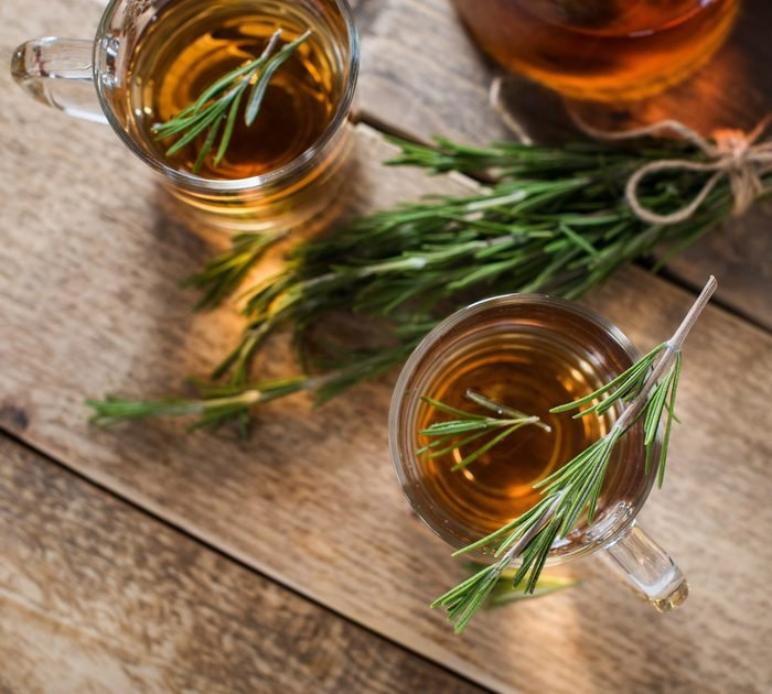 Herbal kombucha tea with aromatic rosemary on wood table