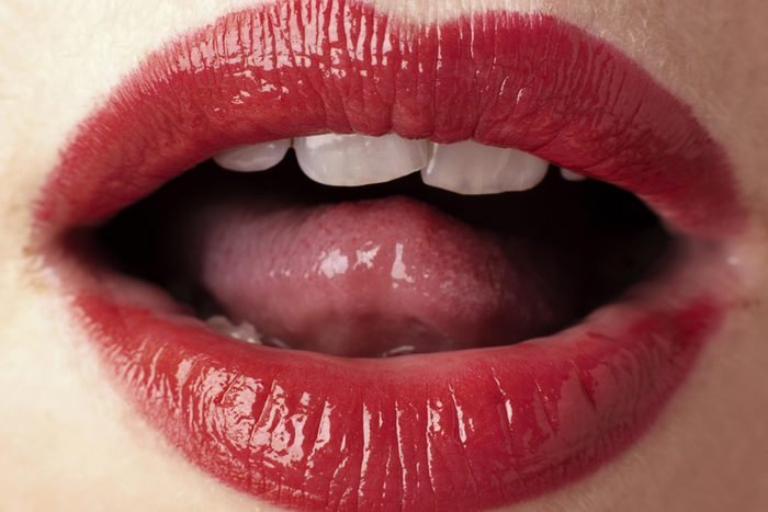 close up of a woman's open mouth, lipstick