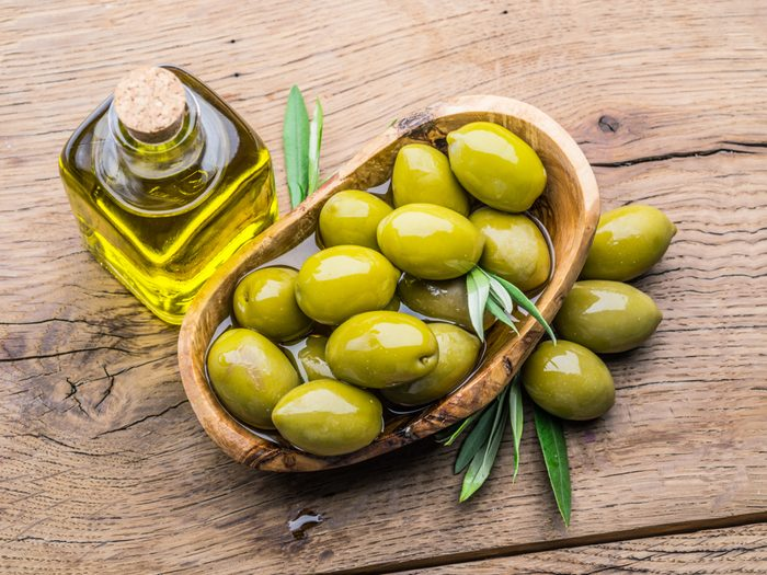 Olives and bottle of olive oil on the wooden table.