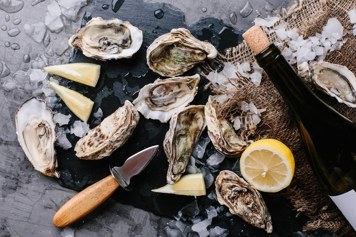 shellfish, lemons and a knife on a wooden cutting board