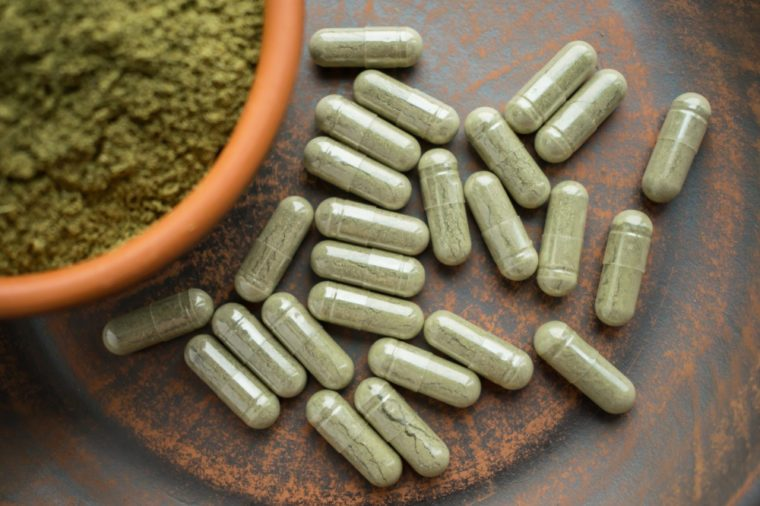 Green capsules and powder on brown plate