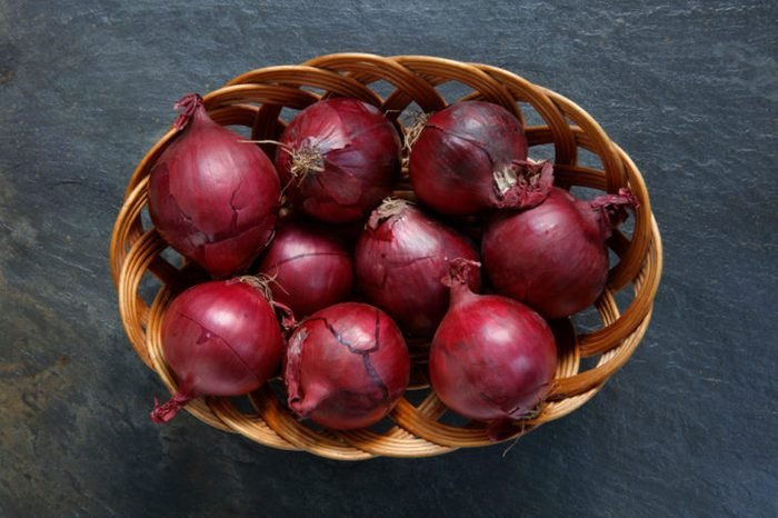 Red onions in wicker basket on slate table top
