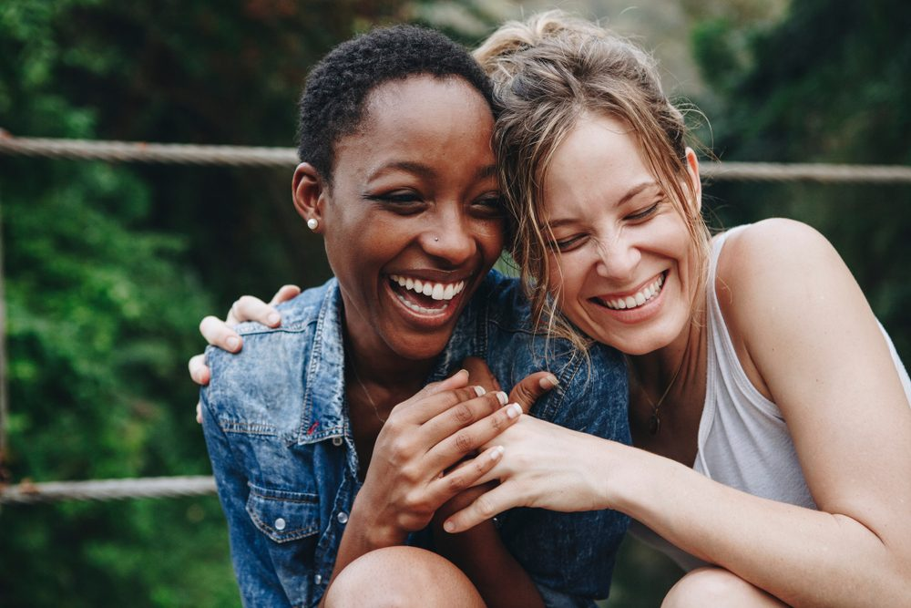 two happy women, laughing and hugging