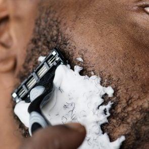 Black man shaving his beard