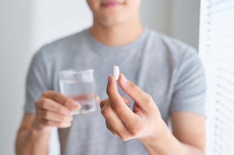 Man holding a white pill and a glass of water