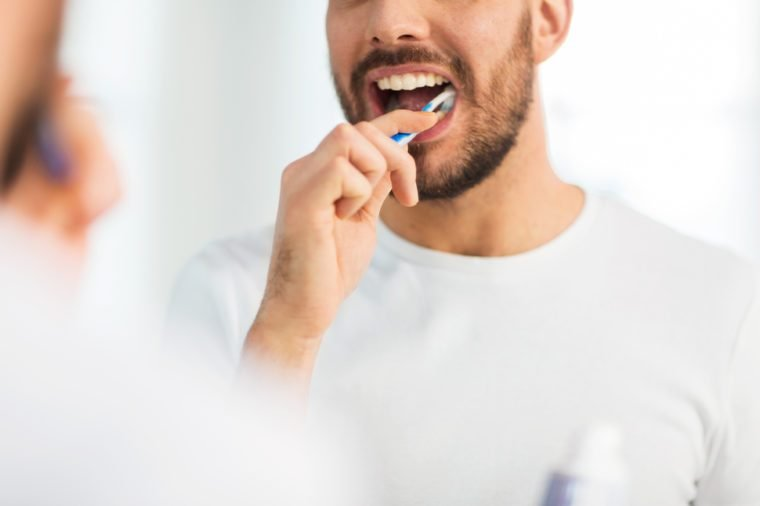 health care, dental hygiene, people and beauty concept - close up of young man with toothbrush cleaning teeth and looking to mirror at home bathroom