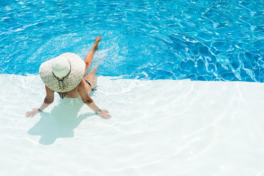 woman in hat sitting at the edge of a swimming pool