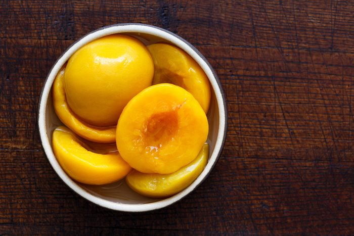 Canned peach halves in bowl isolated on dark background. From above.