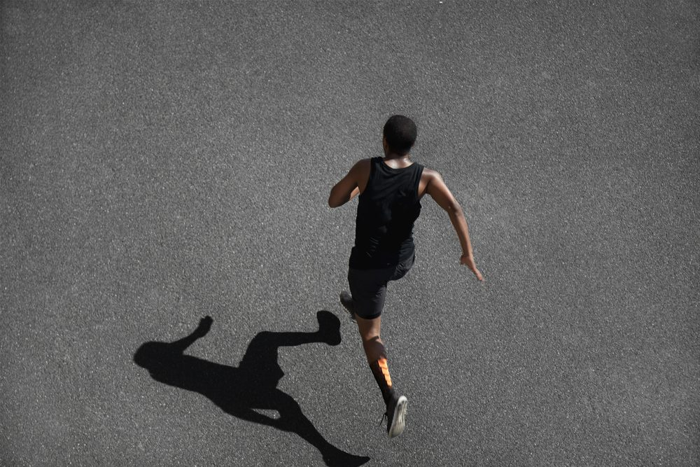 Top view of running man sprinting for success on run. Muscular runner or jogger dressed in black outfit, training at fast speed on black asphalt. Fit sport model exercising sprint outdoors