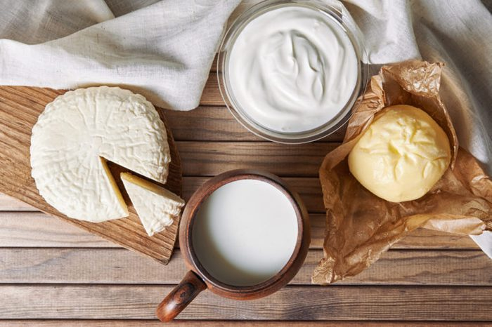 milk, cheese, yoghurt and butter on wooden background. top view