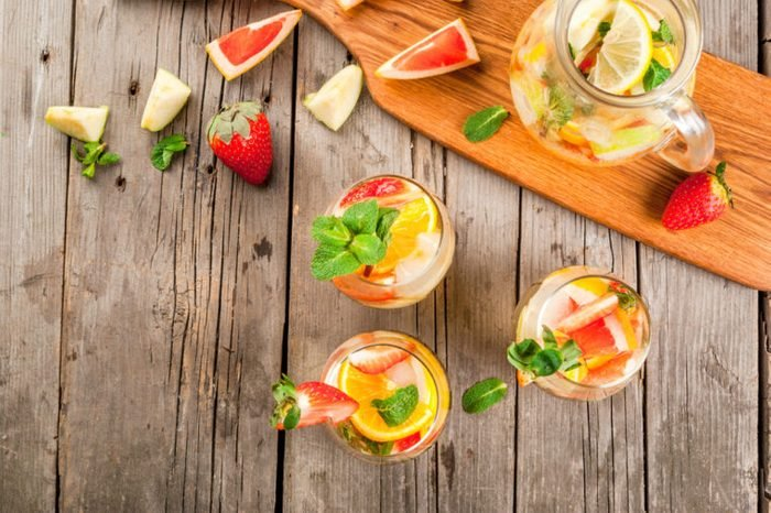 Pitcher and glasses of white sangria with slices of fruit