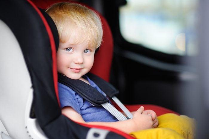 Portrait of pretty toddler boy sitting in car seat. Child transportation safety
