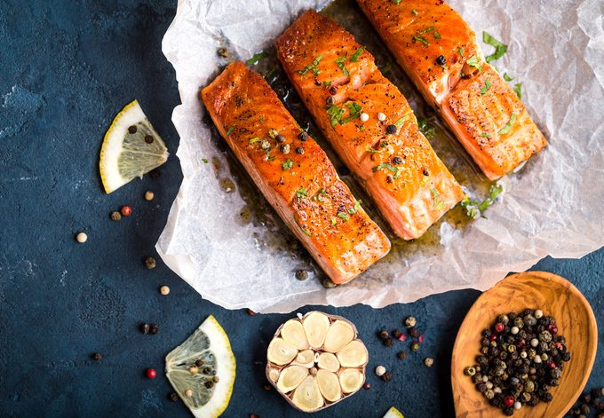 Delicious fried salmon fillet, seasonings on blue rustic concrete background. Cooked salmon steak with pepper, herbs, lemon, garlic, olive oil, spoon. Grilled fish. Fish for healthy dinner. Close-up