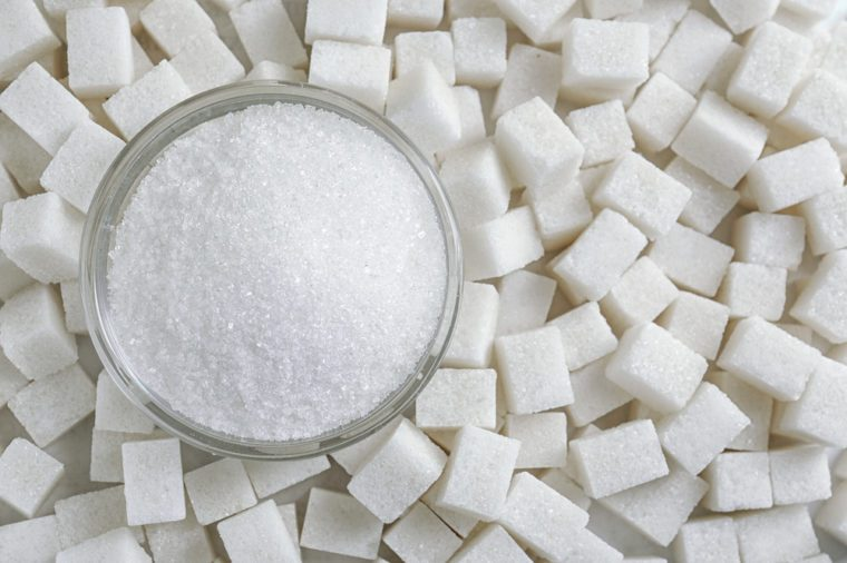 Granulated sugar in jar on sugar cubes