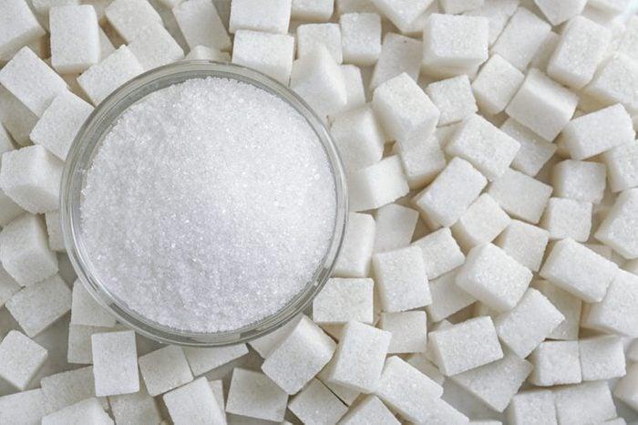 Granulated sugar in jar on sugar cubes