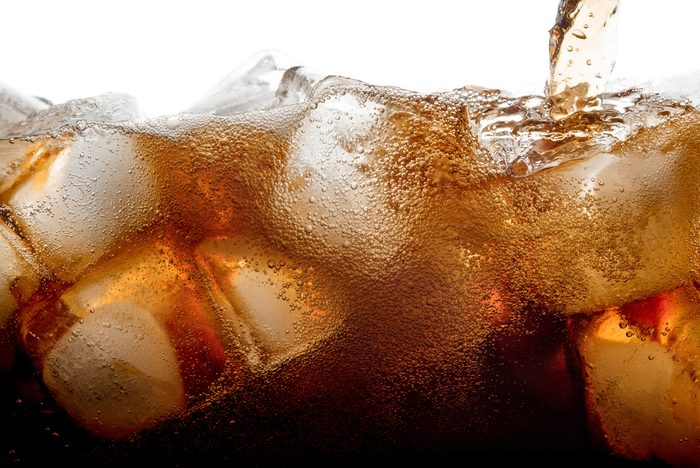 Pouring cola soda with ice and bubble on front view white background cold drink beverage