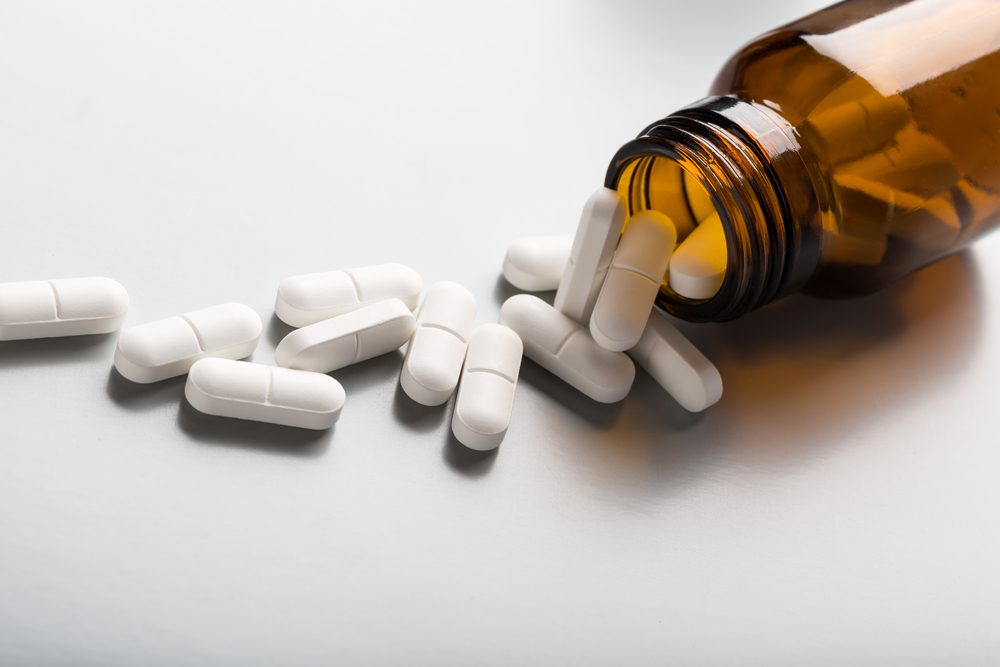 Brown glass bottle with white pills spilling out