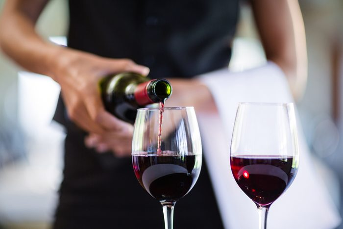 Mid section of waitress pouring red wine in a glass in restaurant