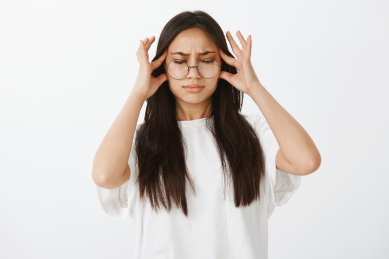 Trying pull emotions together. Studio shot of displeased unhappy european woman in glasses, closing eyes and holding fingers on temple while suffering migraine or headache, waiting for painkillers