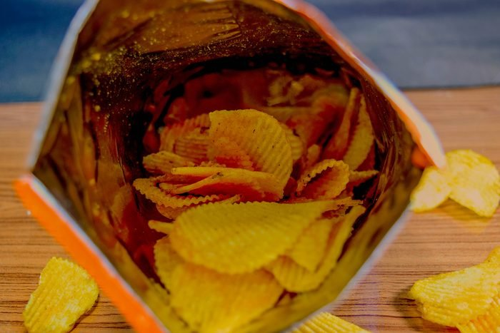 Potato chips in bag And outside the bag On a wooden table