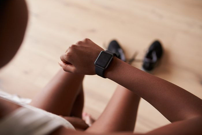 Over-shoulder view of young black woman checking smart watch
