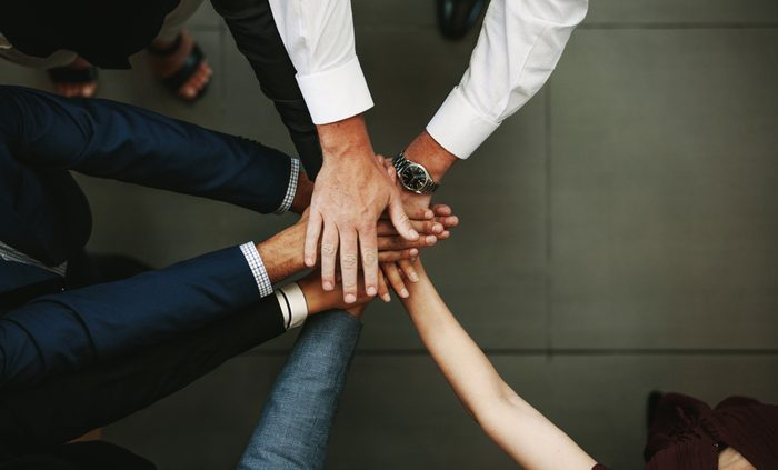 Unity and teamwork Concept. Top view of business people putting their hand together.