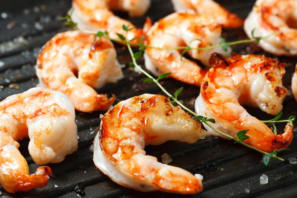 Grilled tiger shrimps on grill with spiced and lemon