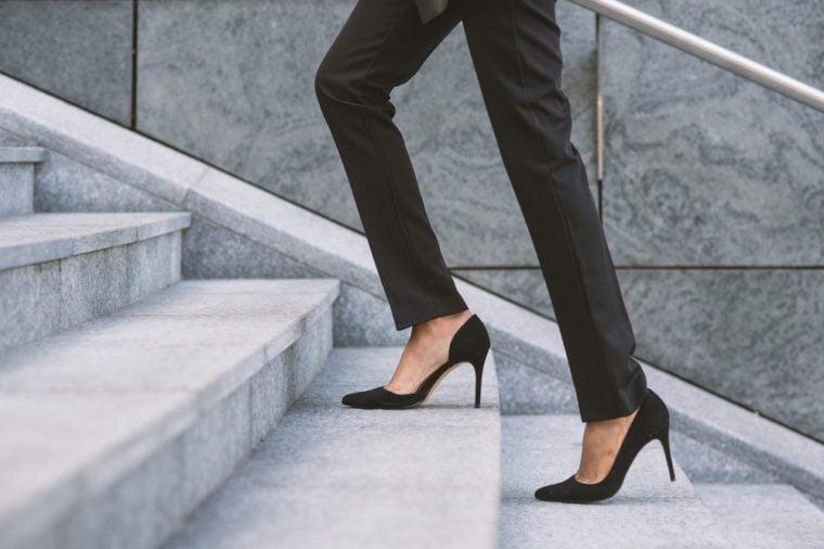 Businesswoman climbing a flight of stairs outdoors.