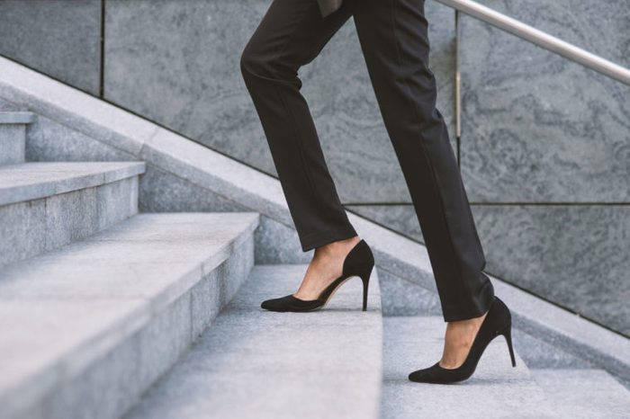Businesswoman climbing a flight of stairs outdoors.