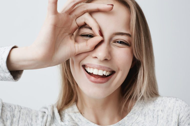 Woman smiling, looking at the camera through fingers in okay gesture