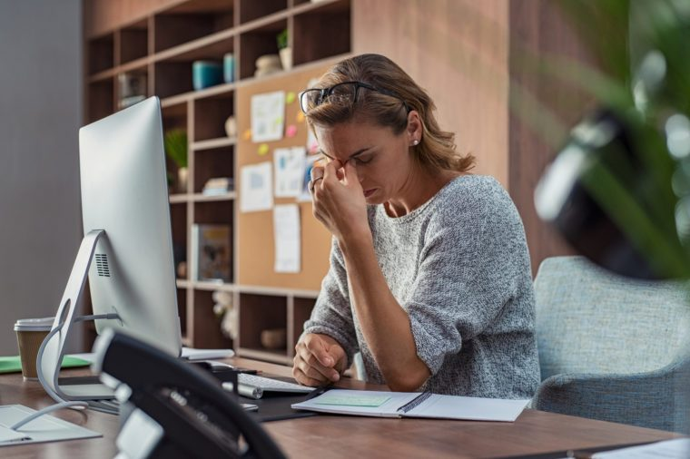 woman with anxiety headache trying to work