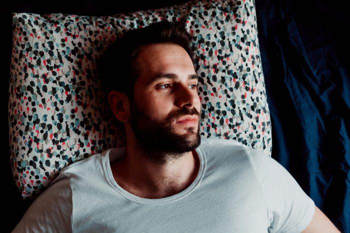 man laying awake in bed