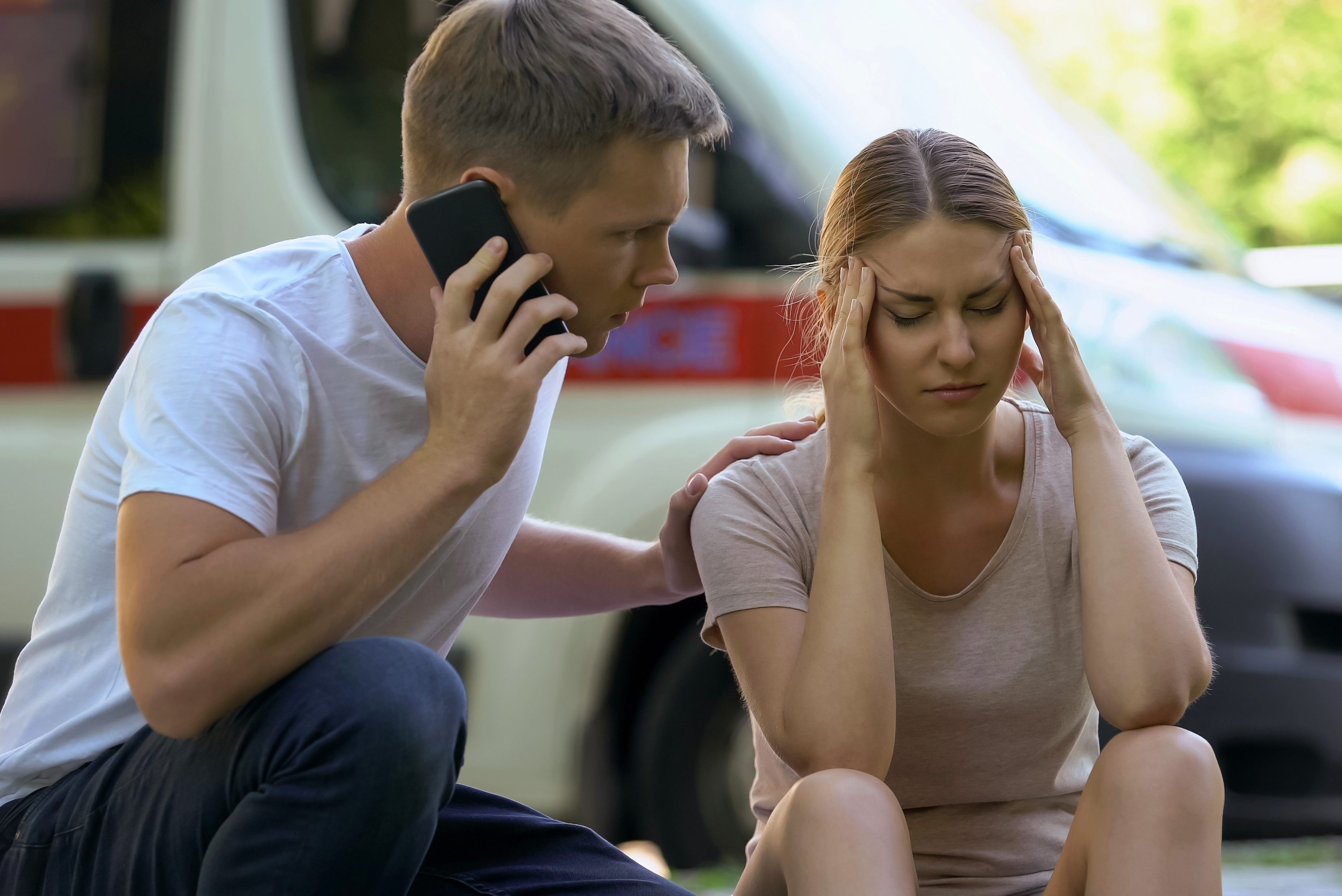 man calling an ambulance for woman in pain