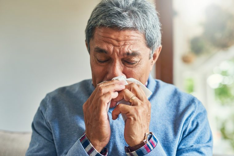 senior man sick with a cold at home