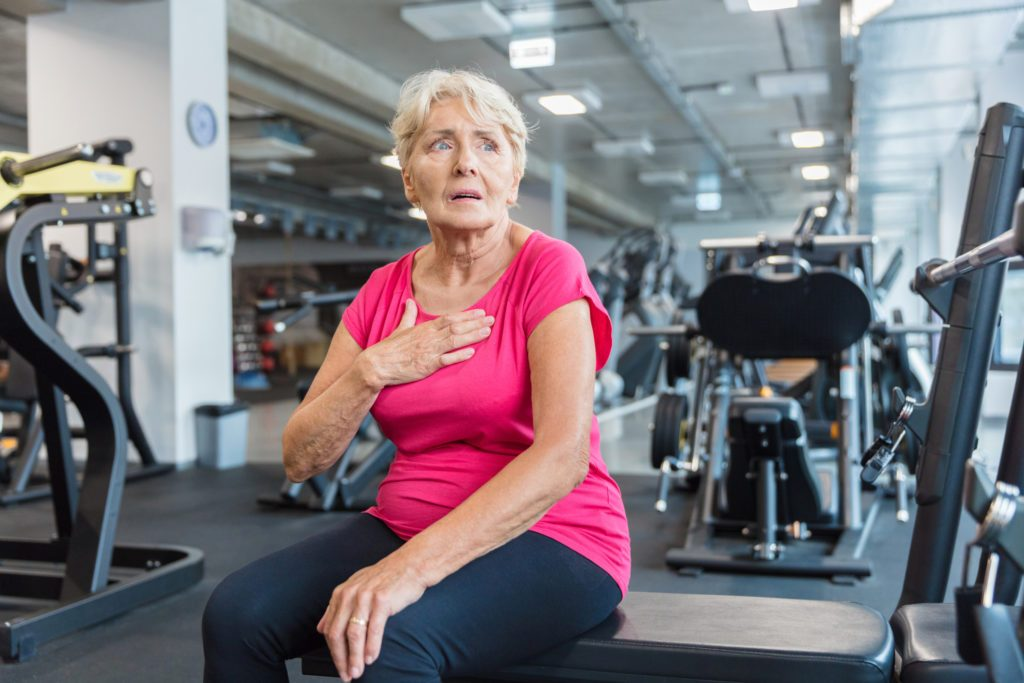 woman suffering from shortness of breath in the gym