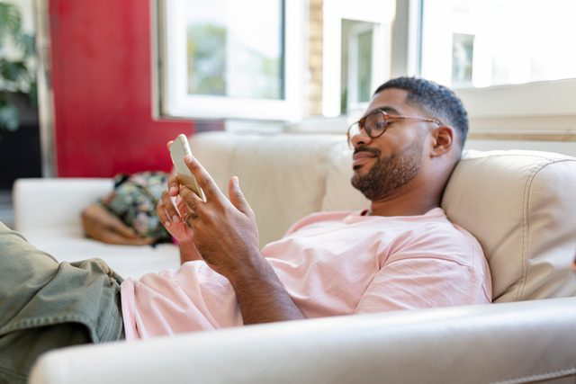 man laying on couch looking at social media on phone